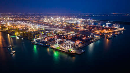 seaport terminal storage containers and shipping cargo containers loading and unloading business services transportation international by the sea at night aerial top view