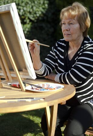 Senior citizen with easel and brush painting in the open Stock Photo - 8927157
