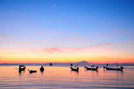 Golden sunset on a sea with silhouette of ships at Suratthani