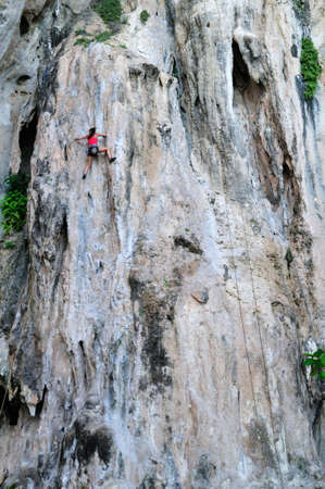 woman on cliff, Phra Nang beach in Railay, Thailand