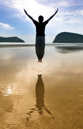 Man jump and raise arms on beach photo
