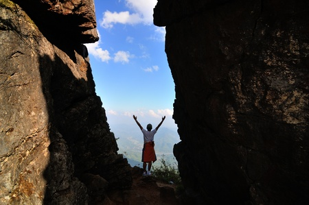 hiker at the mountain pass of a rock with his hands raised