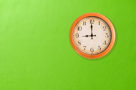 Clock showing 9 o clock on a green wall
