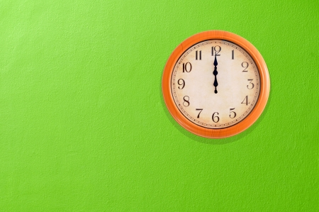 12 o clock: Clock showing 12 o clock pm on a green wall