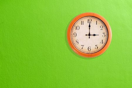 Clock showing 3 o clock on a green wall