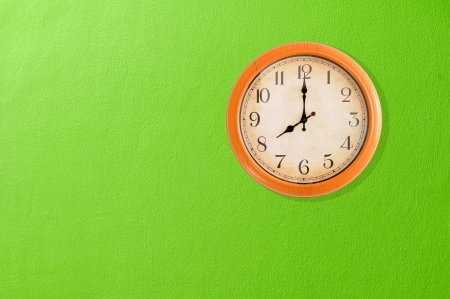 Clock showing 8 o clock on a green wall  Stock Photo
