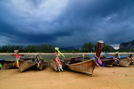 Boats on beach with stormy cloudscape in the background at Krabi, Thailand