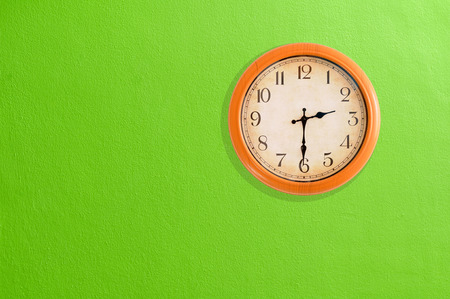 Clock showing 02 30 on a green wall  Stock Photo
