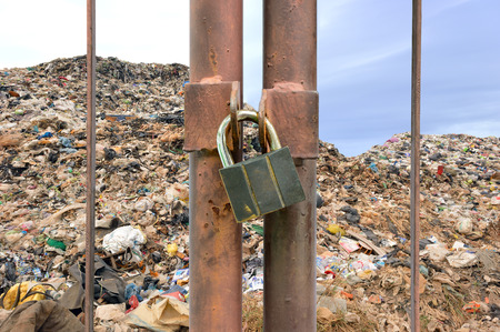 lock key on rusty fence and garbage mountain background photo