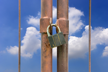 lock key on rusty fence and blue sky background photo