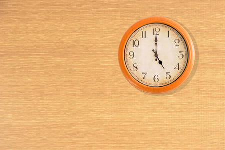 Clock showing 5 oclock on a wooden wall