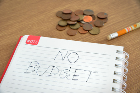 noted: spiral notebook is noted with no budget text a pencil and some coins on wooden table Stock Photo