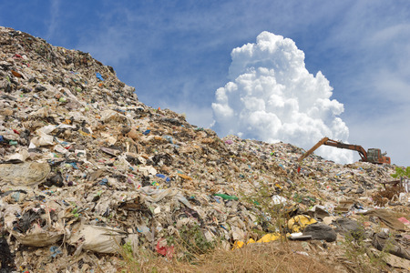dump yard: mountain of garbage with working backhoe Stock Photo