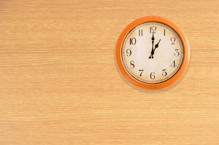 Clock showing 1 oclock on a wooden wall
