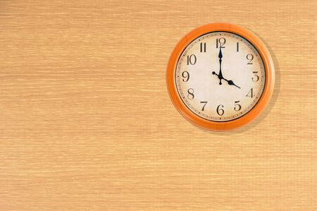 Clock showing 4 oclock on a wooden wall