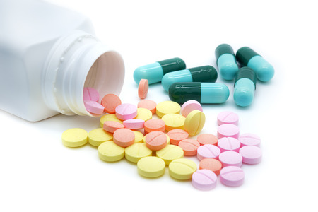 drogadiccion: Píldoras aisladas se derraman fuera de frasco de pastillas Foto de archivo