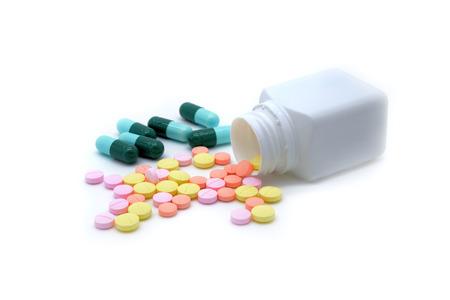 pastillas: Píldoras aisladas se derraman fuera de frasco de pastillas Foto de archivo