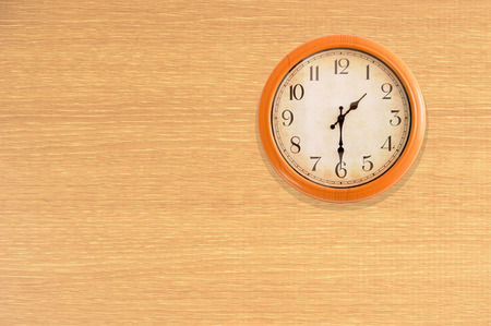 Clock showing 1:30 oclock on a wooden wall