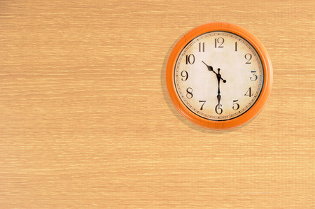 Clock showing 10:30 oclock on a wooden wall Stock Photo