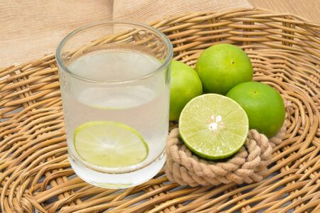 lemon balm: Lemonade with fresh green lemon on rattan basket Stock Photo