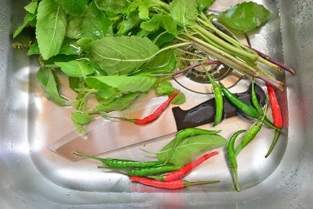 Soaking vegetables in kitchen sink Stock Photo