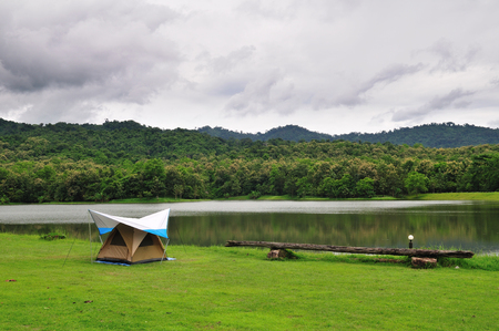 A tent on green grass beside a lake Stock Photo