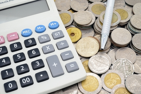 calculator with a pen on stack of coins