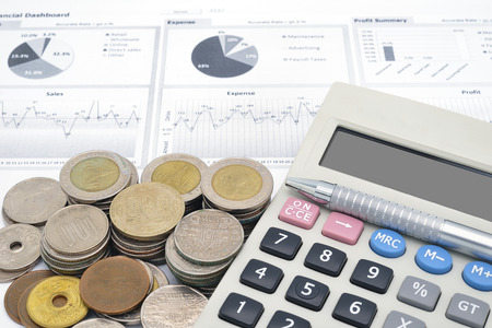 calculator and stack of coins on white paper of financial graph
