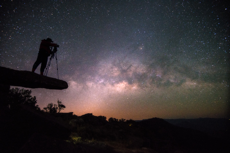 loei: Cameraman takes photo of milky way on Stone lodge under night sky stars