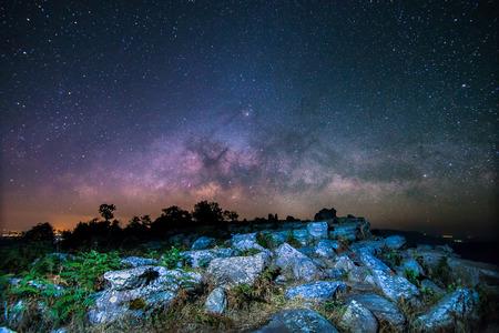 Stone lodge on night sky stars background with milky way