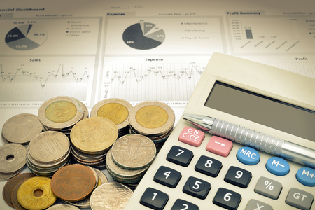 calculator and stack of coins on white paper of financial graph and vignette