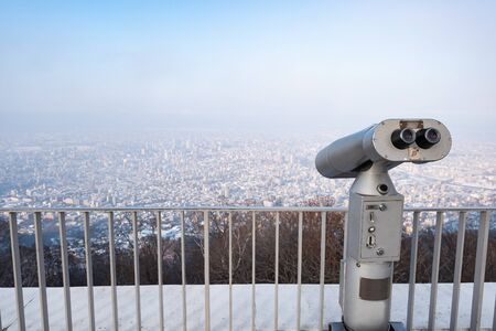 Touristic telescope look at city with view of Moiwa, Hokkaido Japan, on background viewpoint