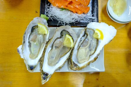 Raw Oysters with lemon on white plate 版權商用圖片