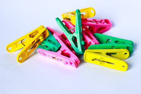 distinct: green, yellow and pink clothes peg isolated on a white background. Stock Photo
