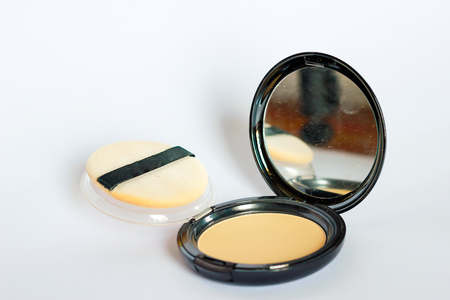 Face powder with sponge and mirror on white background.