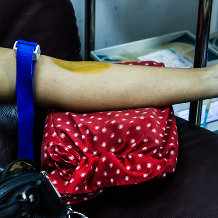 診察室で男性の患者の腕から血液を描く医師のクロップされる画像