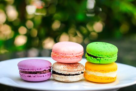 テーブルとコーヒー、カプチーノの上にフランスのマカロンの色のバッチ 写真素材
