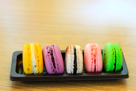 A batch of coloroful French macaroons on a table and Coffee, cappuccino
