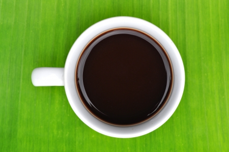 a cup of black coffee on banana leaf  photo