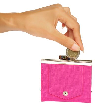 coin purse: A womans manicured hand dropping a coin into a pink purse isolated on white.