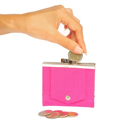 A woman's manicured hand dropping a coin into a pink purse isolated on white. photo