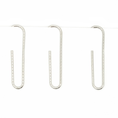 close up of a metal paper clip and paper on white background