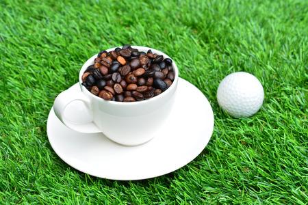 一杯のコーヒーと緑の草の上ゴルフ