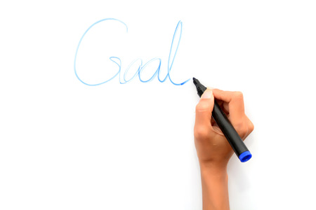 Woman hand writing goals on whiteboard Foto de archivo