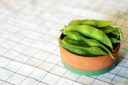 Close up portrait of japanese food edamame nibbles, Boiled green soy beans in ceramic bowl with copy space.