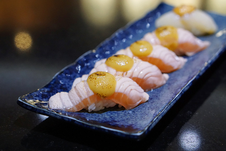 Closeup of salmon aburi sushi topped with saikyo sauce on a blue plate, Aburi style refers to nigiri sushi, the fish is partially grilled topside and partially raw - Japanese food style.