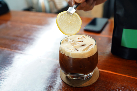 Iced caffe shakerato - A glass of americano mixed with orange juice and topped with lemon sliced on wooden table background.