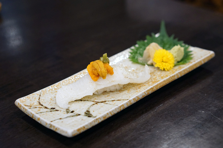 Aburi engawa sushi - Grilled flatfish (Fluke fin) on rice topping with fresh uni served with pickled ginger, Japanese traditional food.