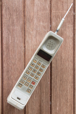phone number: vintage mobile phone on brown wood background.