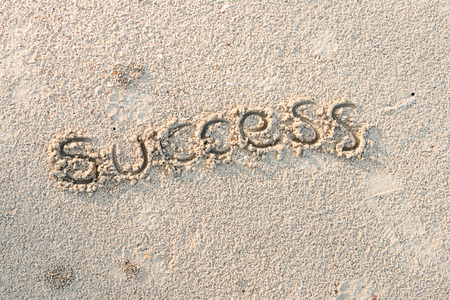 Success write on sand at the beach, Business concept